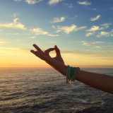 Hand sign in front of beautiful sunset and ocean
