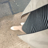 A woman's feet and dress standing on a pavement