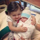 Sister hugging baby brother