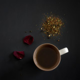Looking down at loose leaf tea and a mug of tea on black background with rose petals