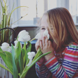 Little girl laughing while smelling fresh cut flowers 💐