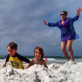 Active mom jumping into sand trap with kids.