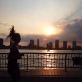 Woman jogging at sunset by the river.