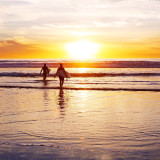 Two surfers walking into the sunset at the beach