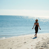 A women wearing a dress walking in the morning at the beach