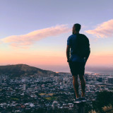Young adult standing on the edge of mountain watching the city scape from high angle at sunset