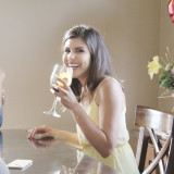 A young woman is drinking a glass of wine.