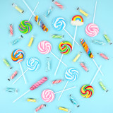 Many colorful lollipops scattered across a turquoise background.