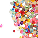 Bright and shiny craft jewels and gems scattered across one side of a white background.