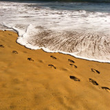 Footprints in the sand, and the oncoming ocean wave