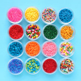 Sixteen different kinds of colorful sprinkles all arranged in little round containers.