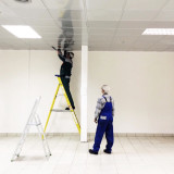 Electricians repair lighting in the trade building