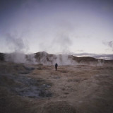 A man stands near the geysers in Uyuni, a province berreen Chile and  Bolivia.