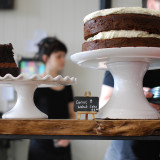 Coffee shop counter displaying large Walnut and Carrot cake. With a waitress in the background.