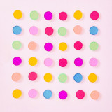 Bright rainbow color circles laid flat in a grid pattern on a light pastel pink background.