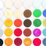 Looking down at full frame shot of round brightly colored artist's pastels pans on bright white background.