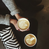Girl wearing cozy sweater warming her hands on an autumn latte.