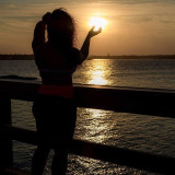 Photo gives the illusion that the young woman is holding the sun in her hand as the sun goes down