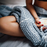 Women sitting in cosy bed with blanket with coffee