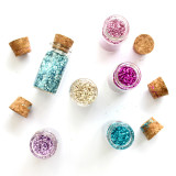 Little glass bottles of colorful glitter on a white background.