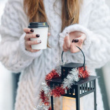 Girl holding hot coffee and decorated lantern