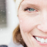Close up of blue / green eyes and smile of woman in her 30's in the snow