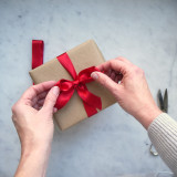 Wrapping a present with a red bow