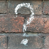 Question mark on brick wall