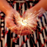 A woman holding a sparkler on 4th of July