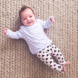 Adorable baby boy in blue striped shirt and black and white patterned leggings on textured cable wool rug.