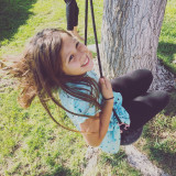 Happy girl having fun on the tree swing!