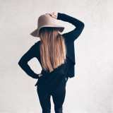 Fashionable girl in black clothing and stylish hat