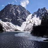 Dragontail Peak and Colchuck Peak above a thawing out Colchuck Lake in the spring in the Alpine Lakes Wilderness near Leavenworth, Washington.