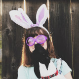 Girl being kissed by puppy, wearing bunny ears, against fence.