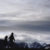 Silhouetted kids playing a top of the Rocky Mountains