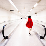 Woman keeping suitcase walking on station subway