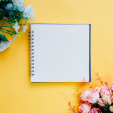 Flat lay of minimal workspace blank notebook with flower on yellow background, spring and summer concept