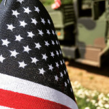 American flag with military vehicle in the background.