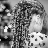 Young girl standing by Christmas tree