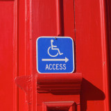 Making the world a better place. Wheelchair accessibility sign on red background.
