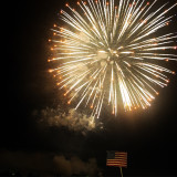 Fourth of July fireworks display while huge USA flag hangs in the background from a crane