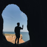 A man in a cave photographs on a mobile phone