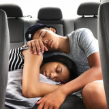 Siblings sleeping in car