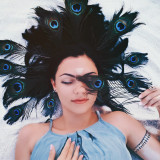 Beautiful girl lying on white sand beach with peacock feathers in hair