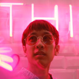 Young hipster man in street style fashion with neon pink light
