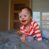Cute baby boy with Down syndrome in the bed