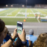 Using mobile device at football game.