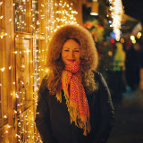 Beautiful portrait of young woman with curly hair on winter illuminated street