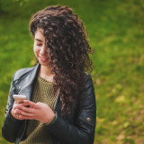 Beautiful young girl with curly hair using mobile phone in the park