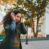 Beautiful young girl with curly hair listening to music with headphones and dancing to the rhythm in the park